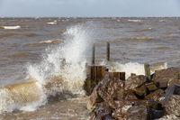 Dutch breakwater with breaking wave in heavy storm