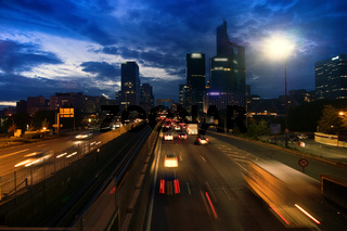 City. Sunset, broken clouds against bright sky, lights of streets