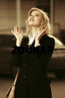 Happy young fashion blond woman in black coat walking in city street