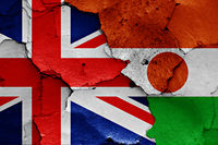 flags of UK and Niger painted on cracked wall
