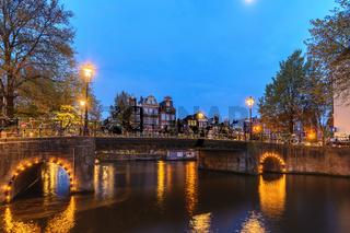 Amsterdam Netherlands, night city skyline Dutch house at canal waterfront