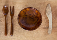 Wooden bowl, knife, spoon and fork on wooden background