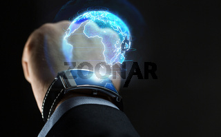 hand with smart watch and earth hologram