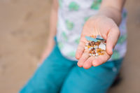Little girl holding tiny harmful plastic microbeads