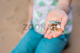 Little girl holding tiny harmful plastic microbeads