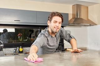 Hausmann beim Putzen der Küche
