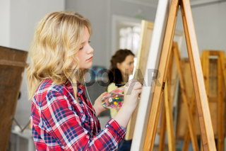girl with easel painting at art school studio