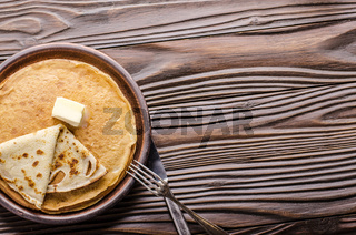 Flat lay view at Stack of French crepes with butter in ceramic dish on wooden kitchen table