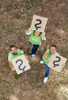 Kreatives Team hält Fragezeichen hoch