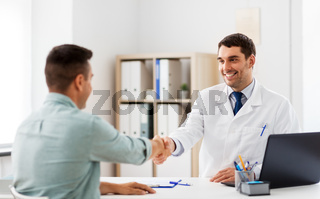 doctor and male patient shaking hands at hospital