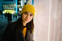 Young woman leans at a illuminated departure plan. Travel,lifestyle and youth concept.