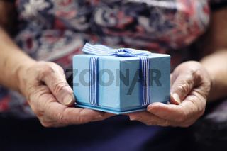 elder woman holding gift