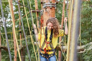 Junge Frau balanciert auf einer Brücke im Kletterwald
