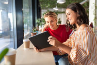 female friends with tablet pc and coffee at cafe
