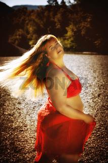 Attraktive übergewichtige Frau in der stilvollen roten Kleidung