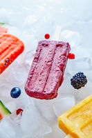 Frozen different fruit juices on a stick on ice cubes with different berries. Sweet healthy dessert. Top view