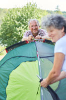 Senior und seine Frau beim Zelt aufbauen