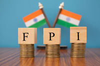 Concept of FPI or foreign portfolio investment on India in wooden block letters on stack of coins with Indian Flag as a background.