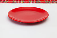 Red plate and Christmas decoration on the white wooden table.