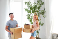 Young happy couple in room with moving boxes