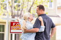 Caucasian Couple Facing and Pointing to Front of Sold Real Estate Sign and House.