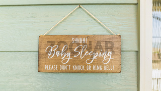 Panorama frame Baby Sleeping sign hanging on the green wall and above the doorbell of a home