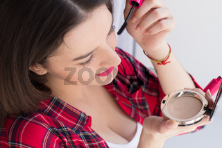 Beautiful girl applying make up.