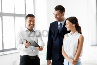 realtor showing tablet pc to customers at office