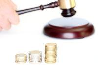 Richterhammer mit Geldmünzen im Stapel
