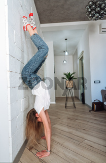 A woman is standing on his hands upside down