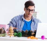 Young man making christmas decoration from cones