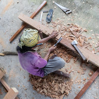 Carpenter working in traditional manual carpentry shop in a third world country.