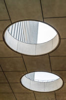 Circular skylights inside a building with view of the concrete exterior wall