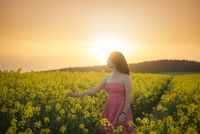 Woman in a rapeseed field at sunset