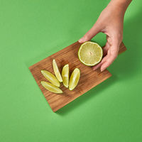 Slices of lime on a board on a green . View from above. A girl's hand takes a half of natural fresh green lime on a wooden brown board.