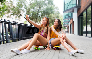 teenage girls taking selfie on city street