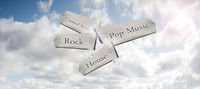 A wooden way-marker sign pointing to different music genres in a blue sky