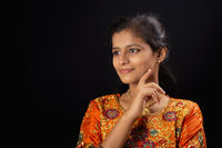 Portrait of a happy young Indian girl smiling on black background with hand on chin.
