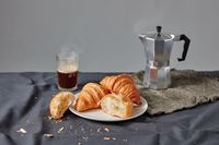 Freshly baked croissants with coffee cup on a dark gray background.