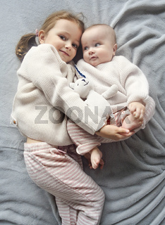 Lifestyle portrait of cute Caucasian girls sisters holding little baby on bed