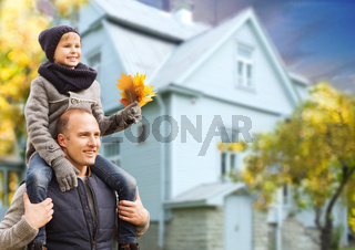 father and son with autumn maple leaves over house