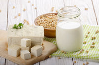 Non-dairy alternatives Soy milk or yogurt in mason jar and tofu on white wooden table with soybeans in bowl aside