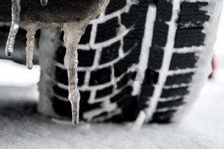 closeup of a tyre of a car with icicle