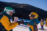 father preparing his little son for the first time on a snowboard