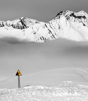 Warning sing on snowy ski slope and mountains in fog
