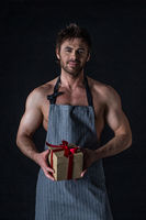 Muscular man in apron holding gift