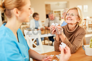 Senior Frau mit Demenz beim Puzzle spielen