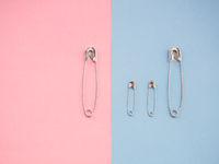 Several safety pins of various sizes in human representation. Concept of traditional family with children