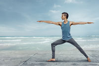 Young handsome man doing yoga at the sea beach