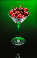 Glass Goblet With Red Cherry On A Green Background